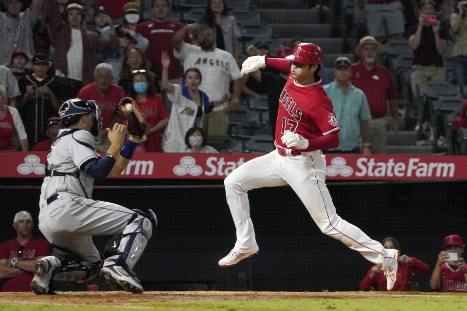 Los Angeles Angels designated hitter Shohei Ohtani, right, avoids a tag by Houston Astros catcher Jason Castro but misses the plate during the 10th inning of a baseball game Wednesday, Sept. 22, 2021, in Anaheim, Calif. Ohtani was later tagged out by Castro. (AP Photo/Mark J. Terrill)