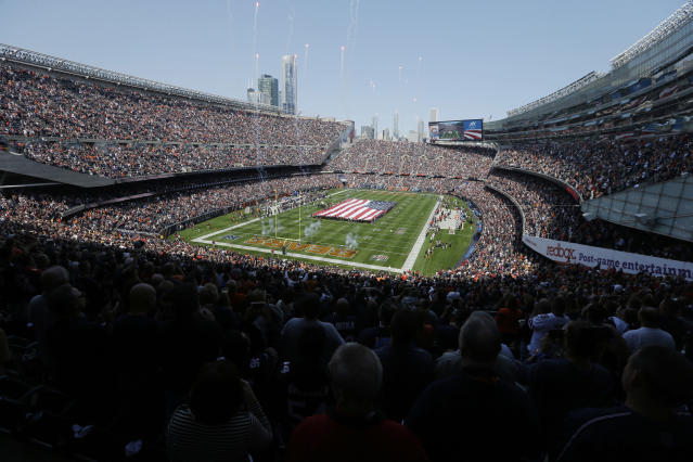 FILE - In this Sept. 10, 2017, file photo, a flag is displayed on the field during the national anthem before an NFL football game between the Chicago Bears and the Atlanta Falcons, in Chicago. Opened in 1924 next to Lake Michigan, Soldier Field became host of the Bears in 1971. (AP Photo/Kiichiro Sato, File)