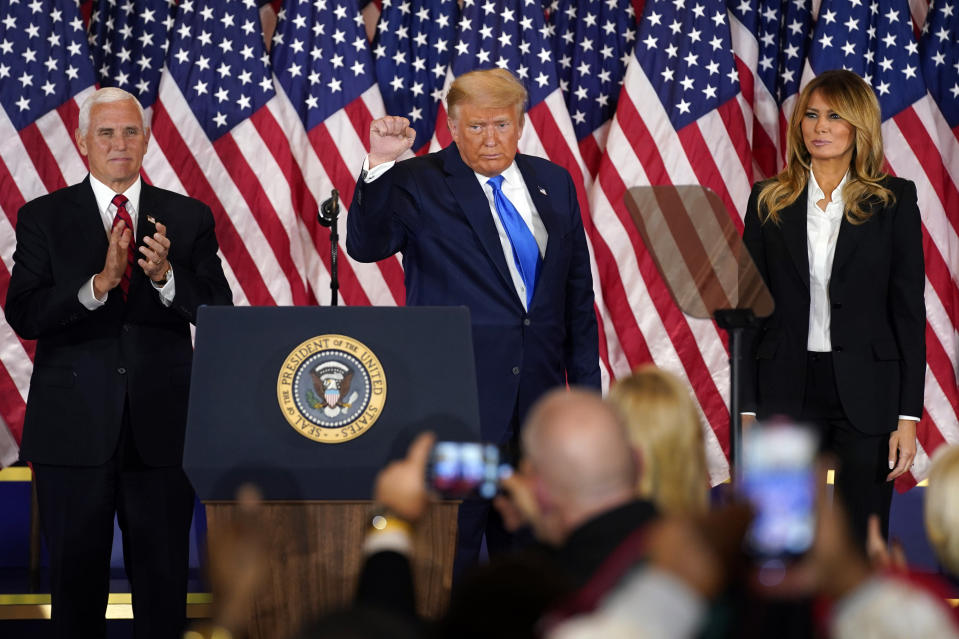 President Donald Trump pumps his fist after speaking in the East Room of the White House, early Wednesday, Nov. 4, 2020, in Washington, as Vice President Mike Pence and first lady Melania Trump watch. (AP Photo/Evan Vucci)