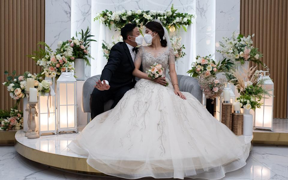 South Korean groom Chang Seung-yun and his Vietnamese bride Nguyen Thi Ut pose a kiss during a wedding ceremony in Seoul, South Korea - Shutterstock