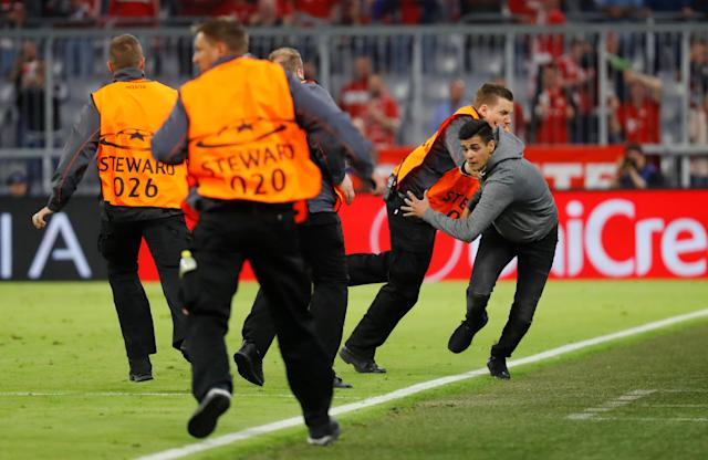 Soccer Football - Champions League Semi Final First Leg - Bayern Munich vs Real Madrid - Allianz Arena, Munich, Germany - April 25, 2018 Stewards tackle a pitch invader after the match REUTERS/Kai Pfaffenbach
