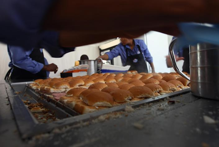"""WASHINGTON, DC - JUNE 14: White Castle employees cook their slider burgers before delivering them at the U.S. Capitol to celebrate the company's 90th anniversary with a """"Castles at the Capitol"""" event June 14, 2011 in Washington, DC. Representatives of the Columbus, Ohio-based company hand-delivered their slider burgers to waiting congressional employees during their lunch hour. (Photo by Win McNamee/Getty Images)"""