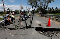 A family rides on a motorcycle through a crack on the street at Kayangan district after earthquake hit on Sunday in North Lombok, Indonesia, August 7, 2018. REUTERS/Beawiharta