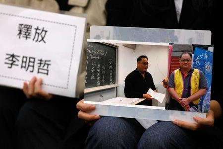 Li Ching-yu, wife of Taiwanese human right activist Li Ming-che, detained in China, holds photos of her husband at a news conference in Taipei,