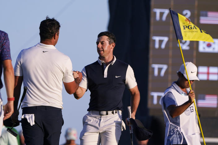 Rory McIlroy, right, of Northern Ireland, shakes the hand of Brooks Koepka, left, after there round on the 18th hole during the second round of the PGA Championship golf tournament on the Ocean Course Friday, May 21, 2021, in Kiawah Island, S.C. (AP Photo/Chris Carlson)