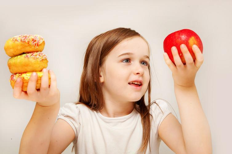 """<span class=""""caption"""">Donuts or an apple? Financial incentives could make the answer easier.</span> <span class=""""attribution""""><a class=""""link rapid-noclick-resp"""" href=""""https://www.shutterstock.com/image-photo/young-girl-enjoys-sandwich-consisting-wholemeal-93698170"""" rel=""""nofollow noopener"""" target=""""_blank"""" data-ylk=""""slk:Shutterstock"""">Shutterstock</a></span>"""