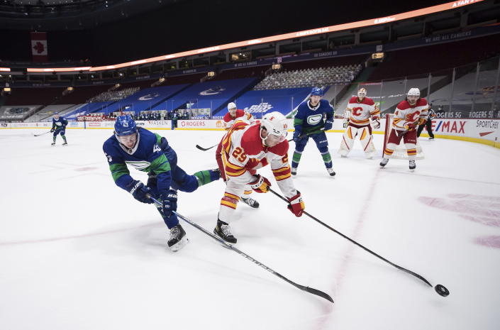 Vancouver Canucks' Quinn Hughes (43) and Calgary Flames' Dillon Dube (29) vie for the puck during overtime of an NHL hockey game, Sunday, May 16, 2021, in Vancouver, British Columbia. (Darryl Dyck/The Canadian Press via AP)