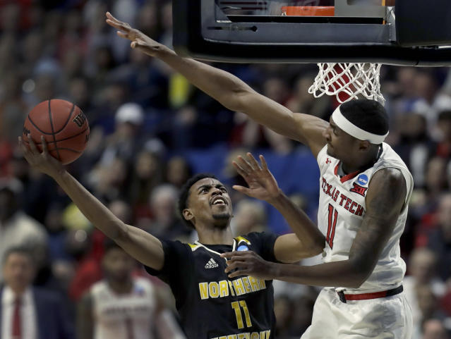 Northern Kentucky's Jalen Tate, left, heads to the basket as Texas Tech's Tariq Owens defends during the second half of a first round men's college basketball game in the NCAA Tournament Friday, March 22, 2019, in Tulsa, Okla. Texas Tech won 72-57. (AP Photo/Jeff Roberson)