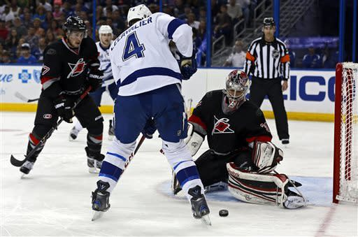 Carolina Hurricanes goalie Dan Ellis, right, makes a save against Tampa Bay Lightning's Vincent Lecavalier (4) during the second period of an NHL hockey game, Sunday, April 21, 2013, in Tampa, Fla. (AP Photo/Mike Carlson)