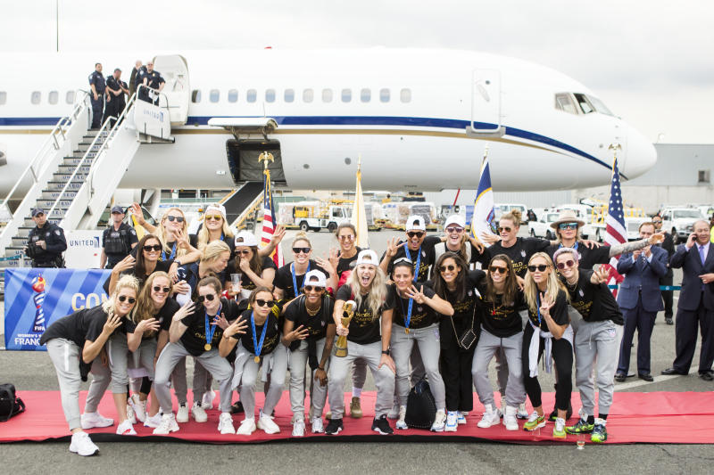 NEWARK, NJ - JULY 08: Julie Ertz #8 of United States holds the FiFA Women's World Cup Championship Trophy and is joined by other members of the U.S. Women's World Cup Championships team wearing a shirt that says World Champions 2019 as the USA Women's National team arrives back in the U.S. after winning their 4th FIFA World Cup title against Netherlands at Newark Liberty International Airport on July 08, 2019 in Newark, NJ, USA. (Photo by Ira L. Black/Corbis via Getty Images)