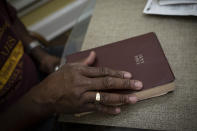 Mike Bishop closes his Bible after reading a passage from the Book of Psalms in Byram, Miss., on Thursday, Oct. 8, 2020. In early July, Bishop was hit by COVID-19. He was exhausted and achy, but never had to be hospitalized. But for Bonnie Bishop, his wife, coronavirus hit like a tsunami. (AP Photo/Wong Maye-E)