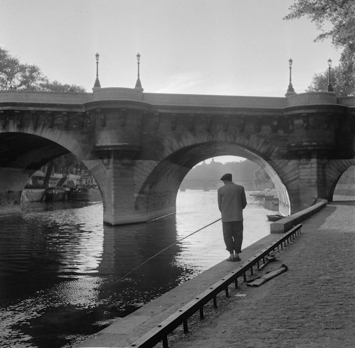 circa 1950: A lone fisherman casts his line into the River Seine under one of Paris's many bridges.