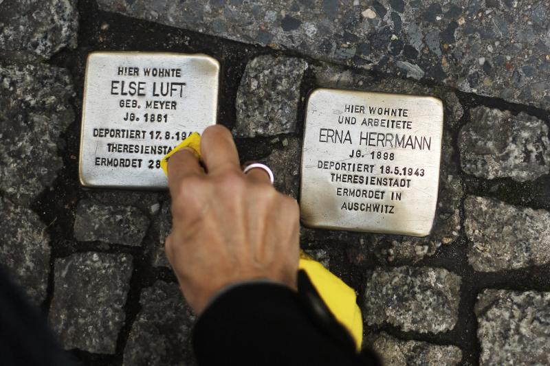 FILE - In this Nov. 9, 2013 file picture a woman cleans a so called 'Stolperstein', or stumbling stone, set by German artist Gunter Demnig, to remember Nazi victims in Berlin, Germany. The epicenter of the Holocaust, the city where Hitler signed the death warrants of 6 million Jews, seems an unlikely candidate for the world's fastest growing Jewish community. But despite this stigma of Nazism, Berlin's dynamic, prosperous present and its rich, pre-World War II Jewish past initially attracted an influx from the former Soviet Union and has continued with the arrival of thousands of Israelis and smaller numbers of often young immigrants from Australia, France, the United States and elsewhere. (AP Photo/Markus Schreiber,File)