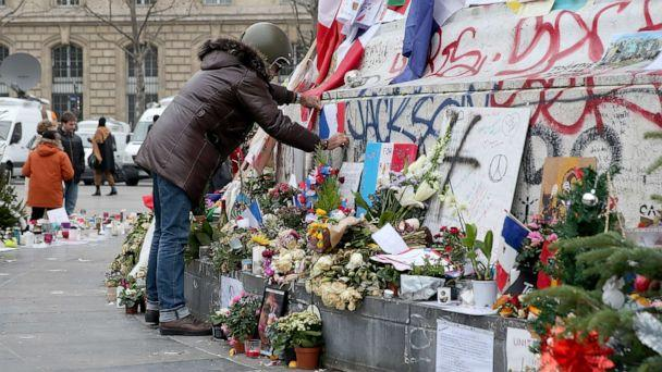 PHOTO: A man is seen posting a French flag on the monument of the 'Place de la Republique' where people continue to pay tribute to the Paris Attacks victims one month after they occurred, Dec. 13, 2015, in Paris. (Pierre Suu/Getty Images)