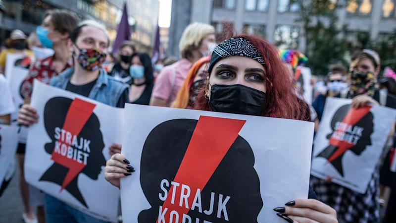 """Protesters hold banners reading """"Women's Strike"""" as they take part in protest against the Polish government plans to withdraw from the Istanbul Convention on prevention and combatting of home violence, in Warsaw, Poland on July 24, 2020. (Photo by Wojtek RADWANSKI / AFP) (Photo by WOJTEK RADWANSKI/AFP via Getty Images) ©Wojtek Radwanski/AFP/Getty Images"""