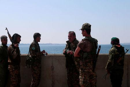 Syrian Democratic Forces (SDF) fighters stand at the northern part of the Tabqa Dam on the Euphrates River