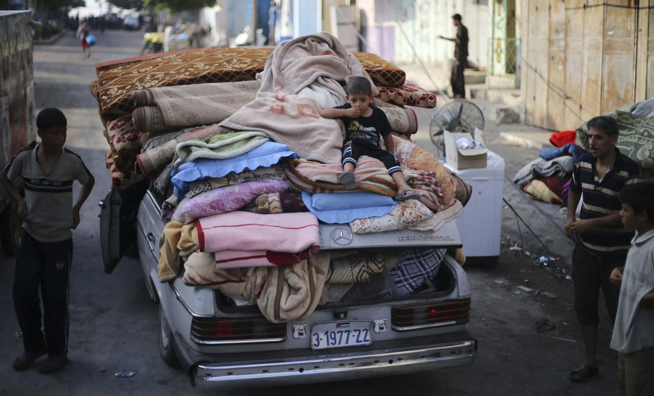 A Palestinian boy sits atop a car loaded with his family's belongings near their house, which witnesses said was hit by an Israeli air strike, in Rafah in the southern Gaza Strip August 26, 2014. Israeli air strikes launched before dawn on Tuesday killed two Palestinians and destroyed much of one of Gaza's tallest apartment and office buildings, setting off huge explosions and wounding 20 people, Palestinian health officials said. Israel had no immediate comment on the attacks that took place as Egyptian mediators stepped up efforts to achieve an elusive ceasefire to end seven weeks of fighting. Israel launched an offensive on July 8, with the declared aim of ending rocket fire into its territory. REUTERS/Ibraheem Abu Mustafa (GAZA - Tags: POLITICS CIVIL UNREST TPX IMAGES OF THE DAY)