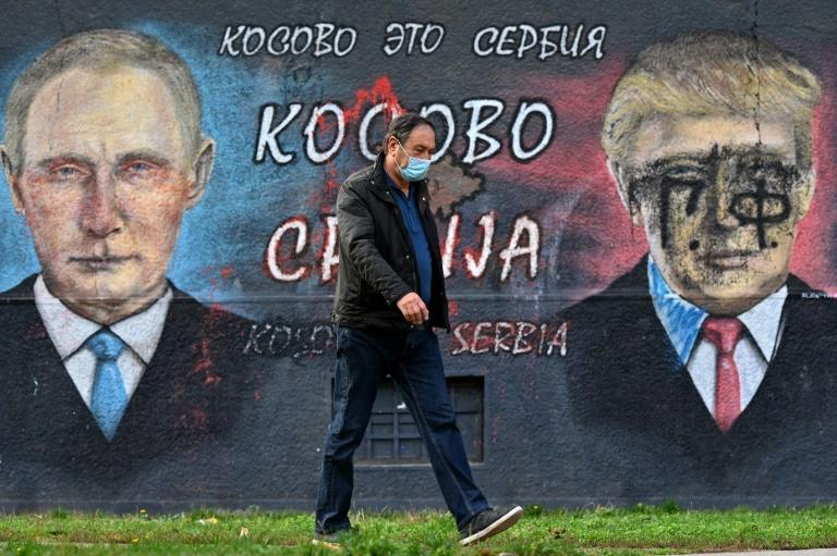 """A pedestrian walks past a mural of Russian President Vladimir Putin and US counterpart Donald Trump bearing the words """"Kosovo is Serbia"""""""