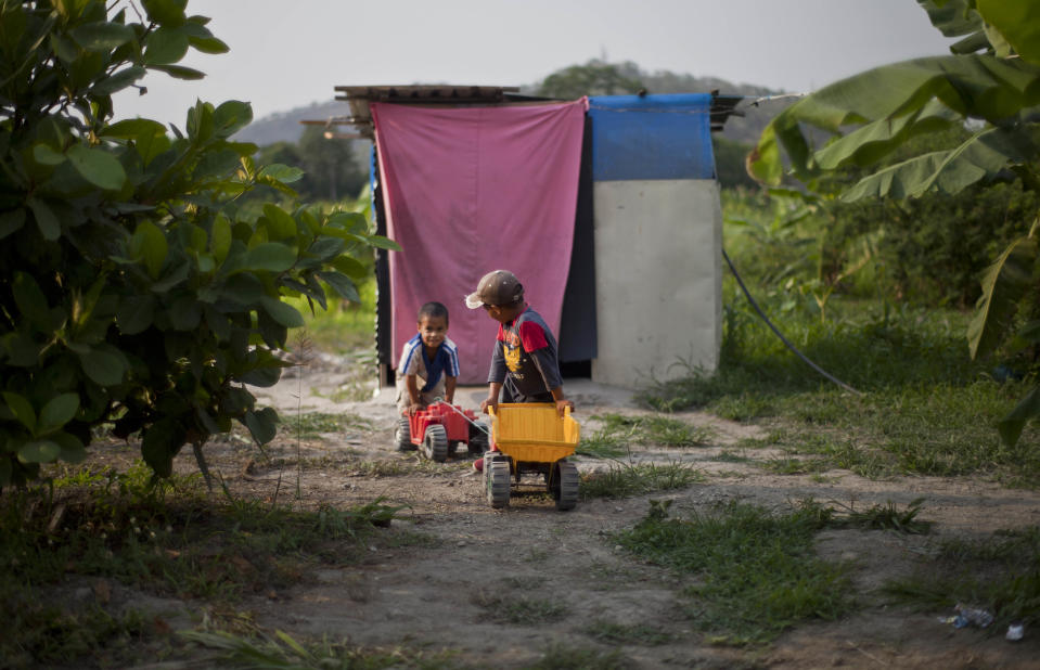 """In this April 8, 2013 photo, two boys push their toy construction vehicles along a dirt path at a squatter settlement near Tacarigua, Venezuela. Outside Venezuela's capital, power outages, food shortages and unfinished projects abound; important factors heading into Sunday's election to replace Venezuela's late President Hugo Chavez, who died last month after a long battle with cancer. An estimated 2 million of the country's nearly 30 million people lack permanent homes, and one of Chavez's anti-poverty """"missions"""" builds them. But it's been slow going. The government says it has built 370,500 homes and apartments over the past two years, and more than 3 million people applied for them. (AP Photo/Ramon Espinosa)"""