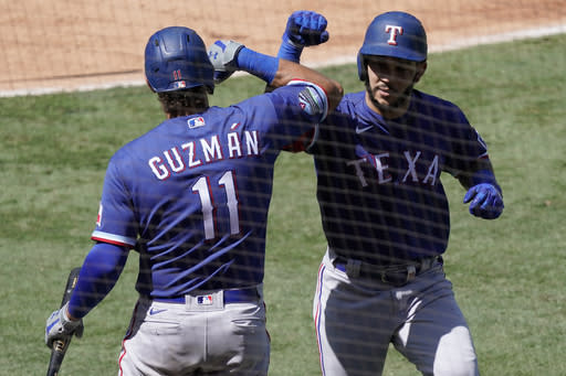 Texas Rangers' Anderson Tejeda, right, gets congratulations from Ronald Guzman, after Tejada hit a solo home run against the Los Angeles Angels, during the second inning of a baseball game in Anaheim, Calif., Sunday, Sept. 20, 2020. (AP Photo/Alex Gallardo)