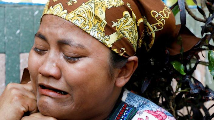 A relative of U Khin Maung Latt cries as she receives his dead body from a hospital in Yangon, 7 March