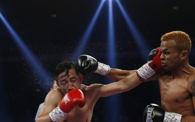 China's double Olympic gold medalist Zou Shiming, left, and Thailand's Amnat Ruenroeng exchange punches during their flyweight title belt boxing match at the Venetian Macao in Macau, Saturday, March 7, 2015. Ruenroeng won the IBF flyweight title belt boxing match. (AP Photo/Kin Cheung)