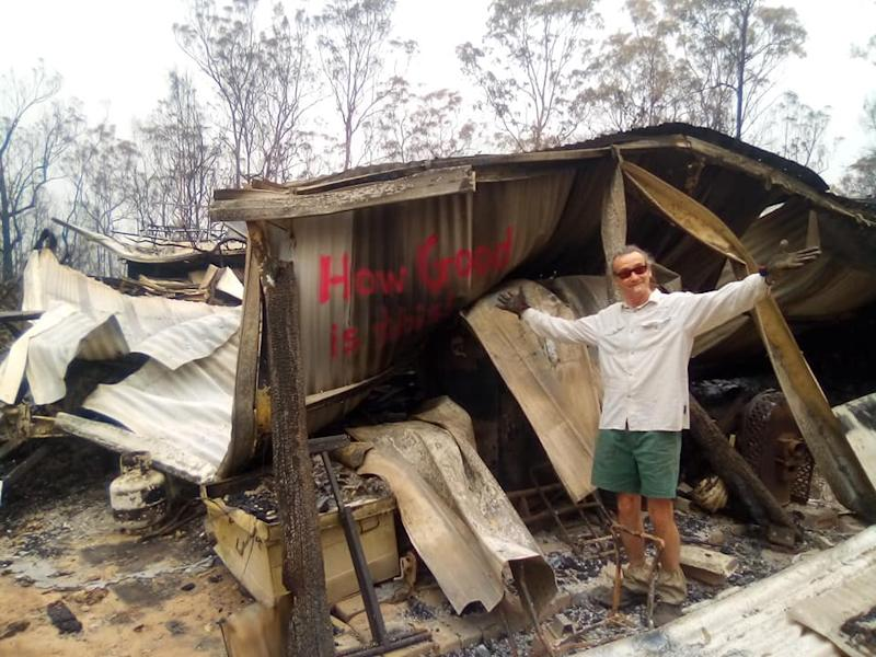 """The Nymboida man stands with bushfire debris from his home. A message saying, """"How good is this"""", is seen scrawled on a piece of corrugated iron."""