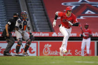 Los Angeles Angels' Shohei Ohtani, right, runs to first as he grounds out while Houston Astros catcher Martin Maldonado, center, and home plate umpire Cory Blaser watch during the third inning of a baseball game Friday, July 31, 2020, in Anaheim, Calif. (AP Photo/Mark J. Terrill)