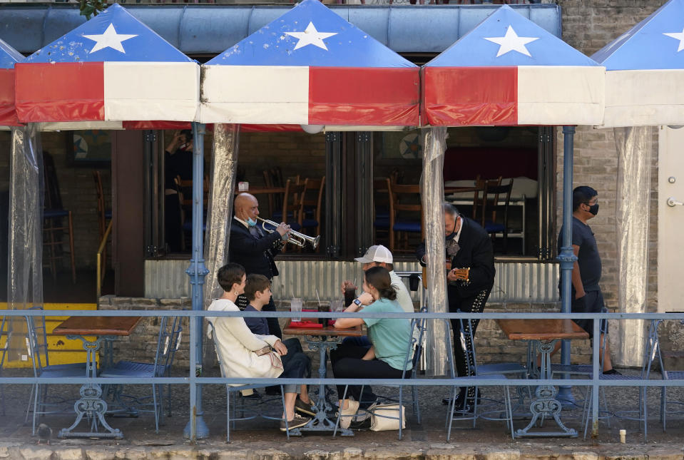 Mariachi perform for diners at a restaurant on the River Walk, Wednesday, March 3, 2021, in San Antonio. Gov. Greg Abbott says Texas is lifting a mask mandate and lifting business capacity limits next week. (AP Photo/Eric Gay)