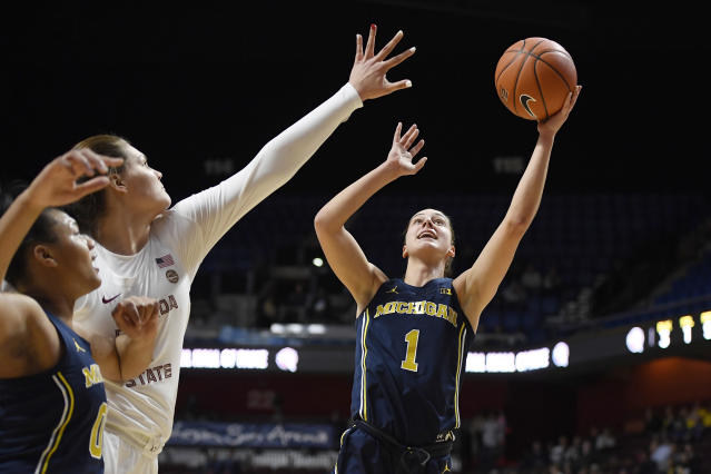 Michigan's Amy Dilk, right, shoots over Florida State's River Baldwin, second from left, as Michigan's Naz Hillmon, left, defends in the first half of an NCAA college basketball game, Sunday, Dec. 22, 2019, in Uncasville, Conn. (AP Photo/Jessica Hill)