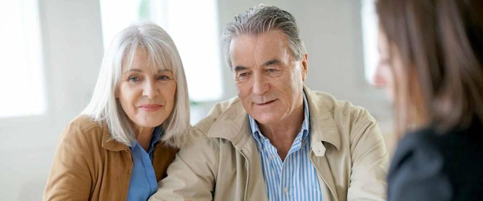 Senior couple meeting financial adviser as she shows them something on a piece of paper.
