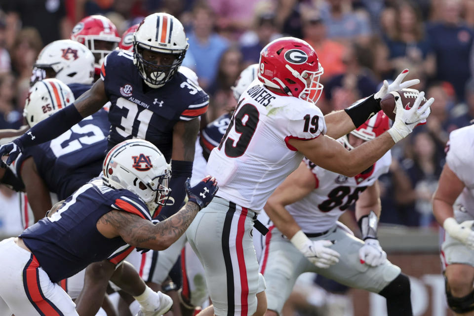 Georgia tight end Brock Bowers (19) catches a pass as Auburn safety Donovan Kaufman (1) defends during the first half of an NCAA college football game Saturday, Oct. 9, 2021, in Auburn, Ala. (AP Photo/Butch Dill)