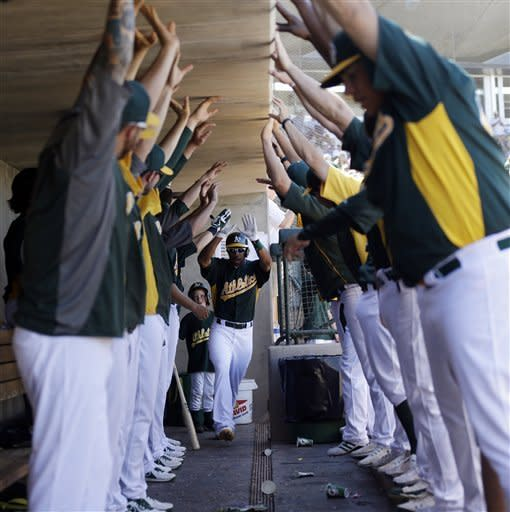 Oakland Athletics' Chris Young, center, celebrates with teammates in the dugout after hitting a grand slam home run against the Milwaukee Brewers during the fourth inning of a spring training baseball game on Monday, March 25, 2013 in Phoenix. (AP Photo/Marcio Jose Sanchez)
