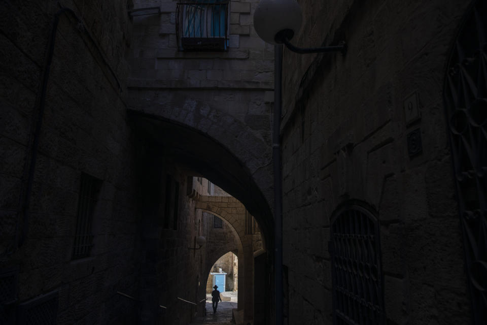 An Ultra-Orthodox Jewish man walks towards the Western Wall, the holiest site where Jews can pray in Jerusalem's old city ahead of Yom Kippur, the holiest day in the Jewish year which starts at sundown Sunday during a three-week nationwide lockdown to curb the spread of the coronavirus, Sept. 27, 2020. (AP Photo/Ariel Schalit)
