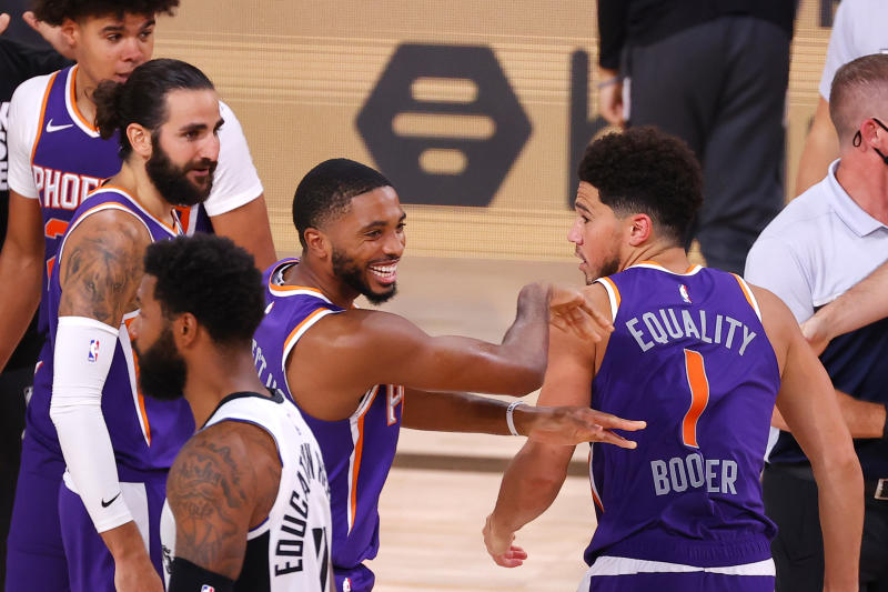 LAKE BUENA VISTA, FLORIDA - AUGUST 04: Devin Booker #1 of the Phoenix Suns celebrates with Mikal Bridges #25 after scoring the game winning basket against the LA Clippers at The Arena at ESPN Wide World Of Sports Complex on August 04, 2020 in Lake Buena Vista, Florida. NOTE TO USER: User expressly acknowledges and agrees that, by downloading and or using this photograph, User is consenting to the terms and conditions of the Getty Images License Agreement. (Photo by Kevin C. Cox/Getty Images)