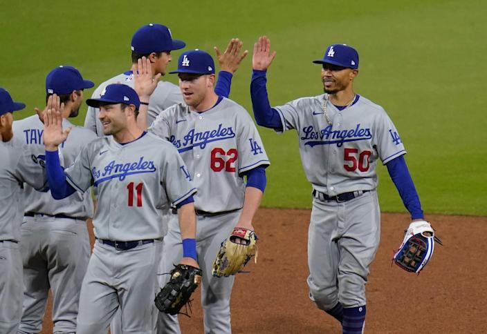 Dodgers center fielder Mookie Betts, right, celebrates with teammates after making the game-saving catch in a 2-0 win over the Padres on Saturday night.
