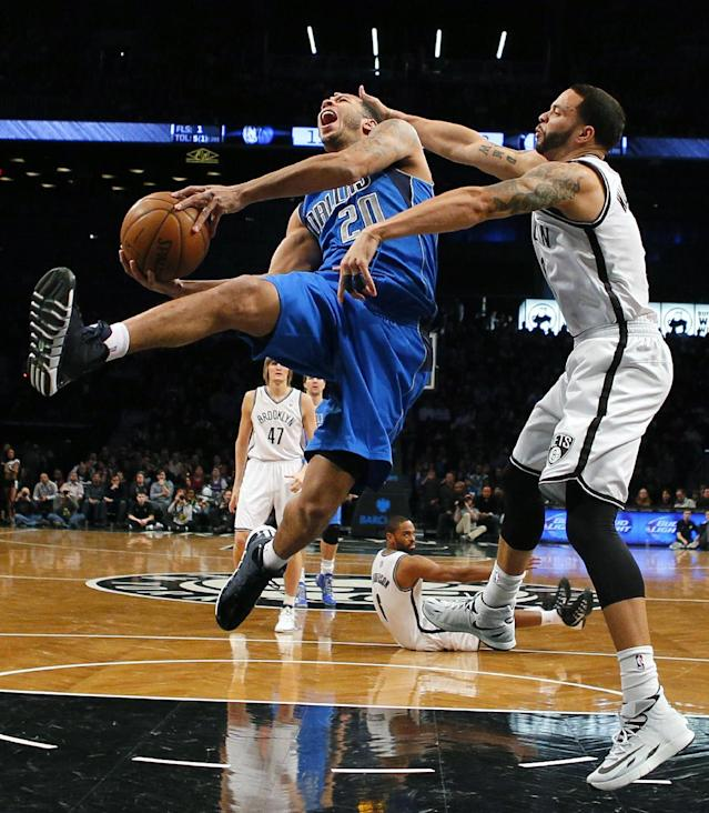 Brooklyn Nets point guard Deron Williams (8) fouls Dallas Mavericks point guard Devin Harris (20) on a layup attempt in the first half of an NBA basketball game on Friday, Jan. 24, 2014, in New York. (AP Photo/Paul J. Bereswill)