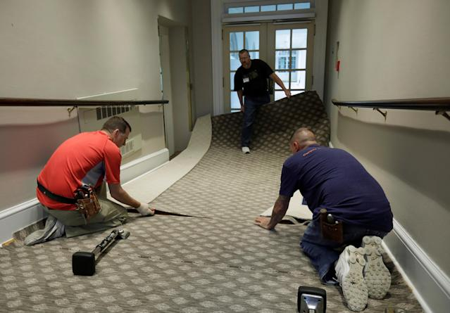 <p>Construction workers lay carpet on a ramp from the West Wing offices to the White House colonnade during renovations at the White House in Washington, Aug.11, 2017. (Photo: Jim Bourg/Reuters) </p>