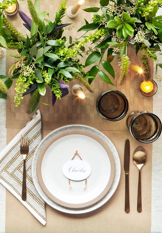 """<p>A <a href=""""https://www.amazon.com/Cotton-Craft-12-Pack-Construction/dp/B07M6NSGWX"""" target=""""_blank"""">patterned napkin</a> and earthy dinner plate are lively enough on their own—so all you'll need to add is the wishbone and a simple white place card on top of them. (The wishbone, by the way, makes for a wonderful favor too.)</p><p><strong>For the wishbone: </strong>Bend a 10-inch piece of armature wire into a """"U"""" shape. Hammer curved end to make a point. Use pliers to bend the point and two ends of wishbone slightly upward. Wrap wishbone in copper foil tape and add place card.<br></p><p><a class=""""body-btn-link"""" href=""""https://www.amazon.com/Silverware-LIANYU-20-Piece-Stainless-Dishwasher/dp/B07FFQ9RHK?tag=syn-yahoo-20&ascsubtag=%5Bartid%7C10050.g.1538%5Bsrc%7Cyahoo-us"""" target=""""_blank"""">SHOP COPPER FLATWARE</a></p>"""