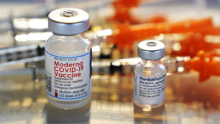 FILE - In this Feb. 25, 2021, file photo, vials for the Moderna and Pfizer COVID-19 vaccines are displayed on a tray at a clinic set up by the New Hampshire National Guard in the parking lot of Exeter, N.H., High School. An untold number of Americans have managed to get COVID-19 booster shots even though the U.S. government hasn't approved them. They're doing so by taking advantage of the nation's vaccine surplus and loose tracking of those who have been fully vaccinated. (AP Photo/Charles Krupa, File)