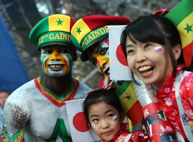 Soccer Football - World Cup - Group H - Japan v Senegal - Ekaterinburg Arena, Yekaterinburg, Russia - June 24, 2018. Fans of Japan and Senegal pose outside the stadium after the match. REUTERS/Marcos Brindicci