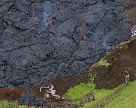 A man takes a picture of the lava flow from Mount Kilauea in Pahoa, Hawaii October 29, 2014. REUTERS/Marco Garcia