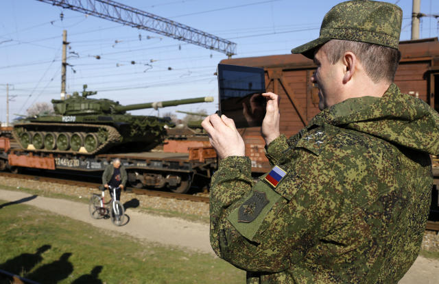 A Russian officer takes photos of Russian tanks as they arrive at a train station in the Crimean settlement of Gvardeiskoye near the city of Simferopol, Ukraine, March 31, 2014.