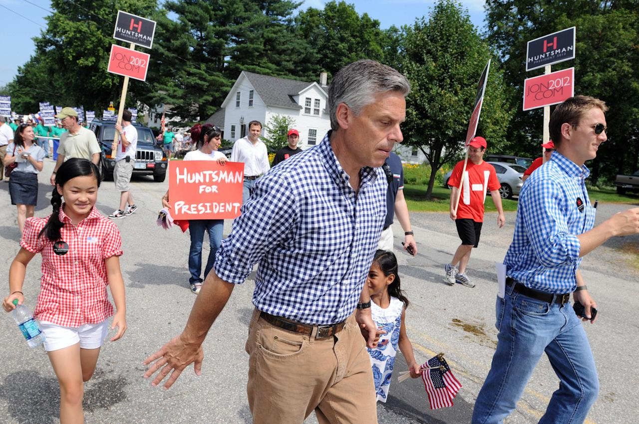 AMHERST, NH - JULY 4: Former Ambassador to China and Republican presidential candidate Jon Huntsman marches in a Fourth of July Parade with daughters Gracie Mei (L) and Asha July 4, 2011 in Amherst, New Hampshire. Huntsman will also be speaking at barbecues during the campaign swing during the holiday.  (Photo by Darren McCollester/Getty Images)
