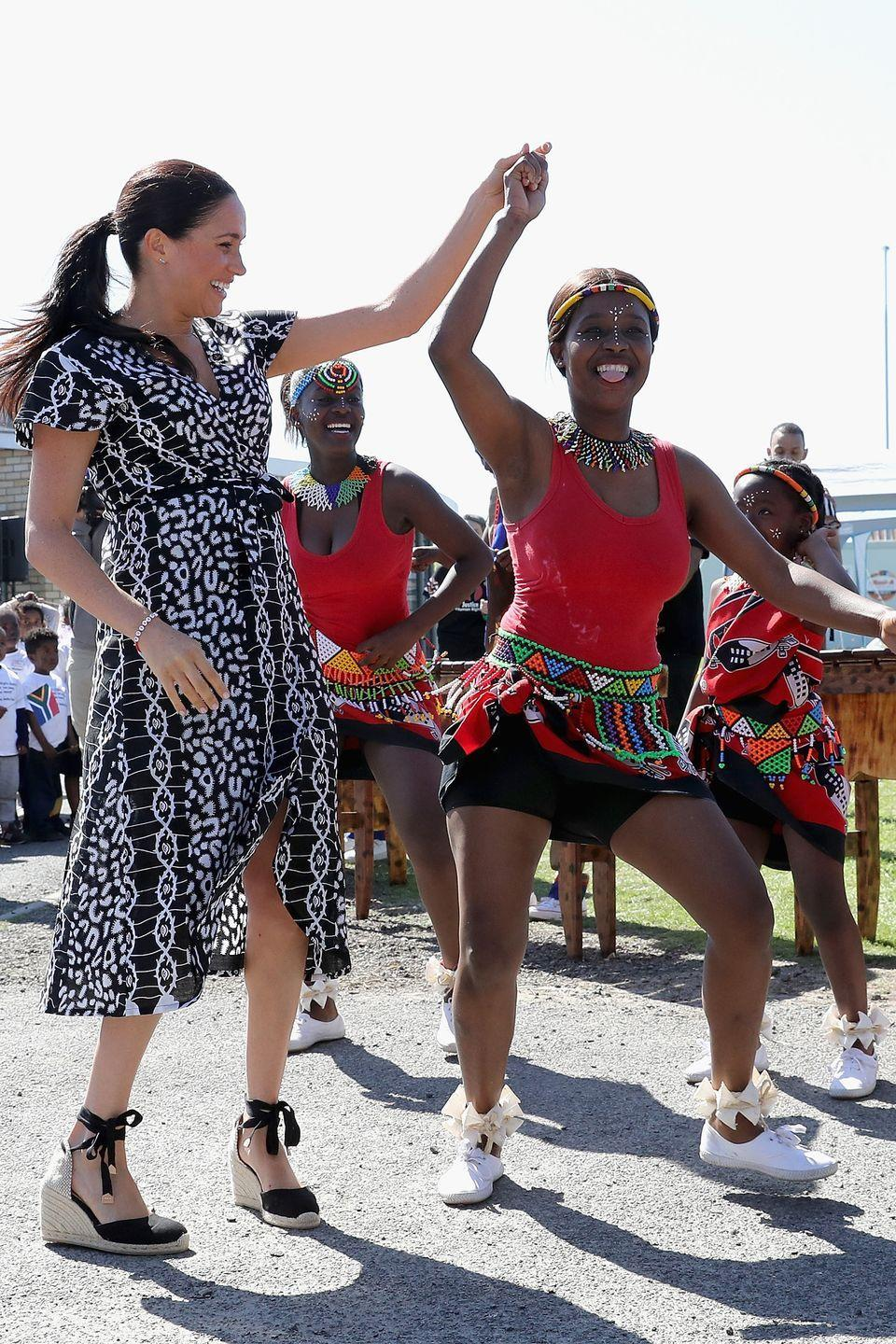 <p>Meghan dances during a visit to the Justice Desk initiative in the Nyanga township of Cape Town, South Africa.</p>