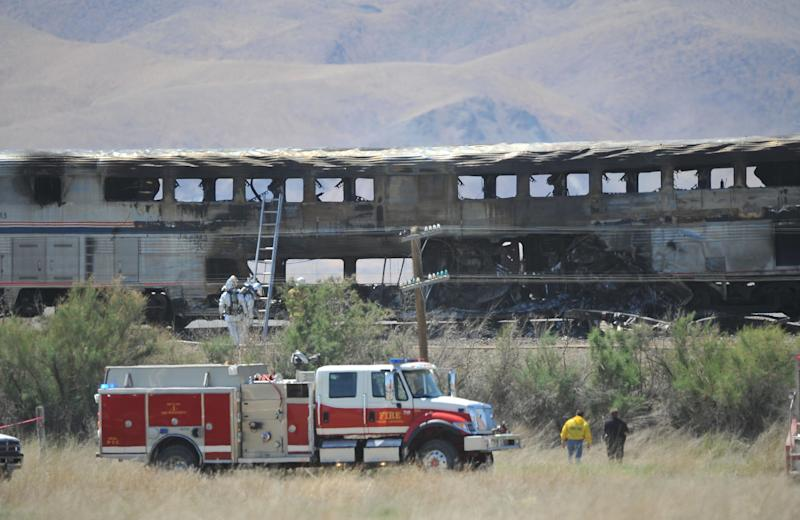 Amtrak passenger cars sit still smoldering after the train was struck by a semi truck on US 95 north of Fallon, Nev., Friday June 24, 2011.  The driver of the truck and a passenger were killed, and officials must let the wreck cool off before they continue their search. (AP Photo/Liz Margerum - Reno Gazette Journal)