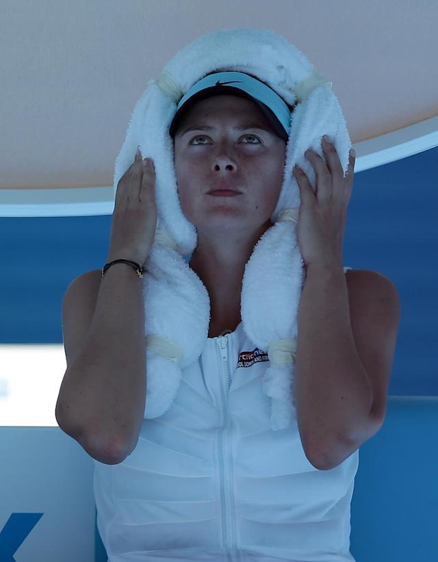 Maria Sharapova of Russia wraps an ice-towel around her head during a break in her second round match against Karin Knapp of Italy at the Australian Open tennis championship in Melbourne, Australia, Thursday, Jan. 16, 2014. Temperatures are expected to top 44cC (112 F) during play today. (AP Photo/Aaron Favila)