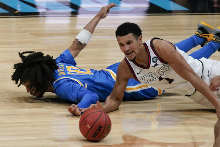 Gonzaga guard Jalen Suggs (1) scrambles for a loose ball with UCLA guard Tyger Campbell (10) during the second half of a men's Final Four NCAA college basketball tournament semifinal game, Saturday, April 3, 2021, at Lucas Oil Stadium in Indianapolis. (AP Photo/Michael Conroy)
