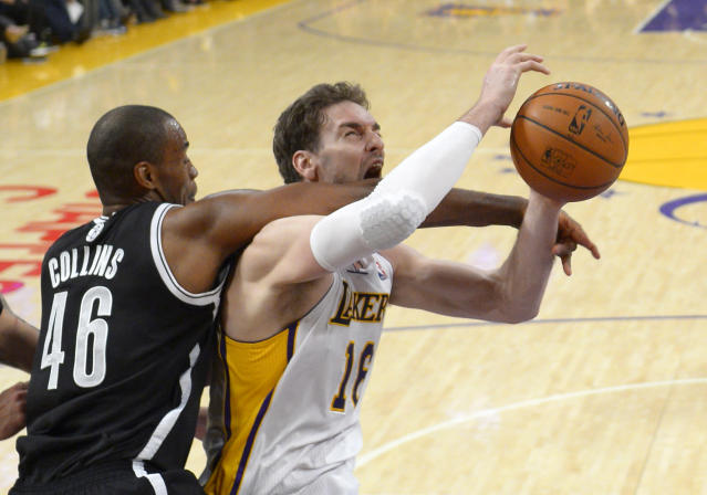 Brooklyn Nets center Jason Collins, left, fouls Los Angeles Lakers center Pau Gasol during the second half of an NBA basketball game, Sunday, Feb. 23, 2014, in Los Angeles. The Nets won 108-102. (AP Photo/Mark J. Terrill)