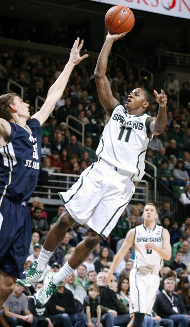 Michigan State's Keith Appling (11) puts up a driving shot against Mount St. Mary's Taylor Danaher, left, during the first half of an NCAA college basketball game, Friday, Nov. 29, 2013, in East Lansing, Mich. (AP Photo/Al Goldis)